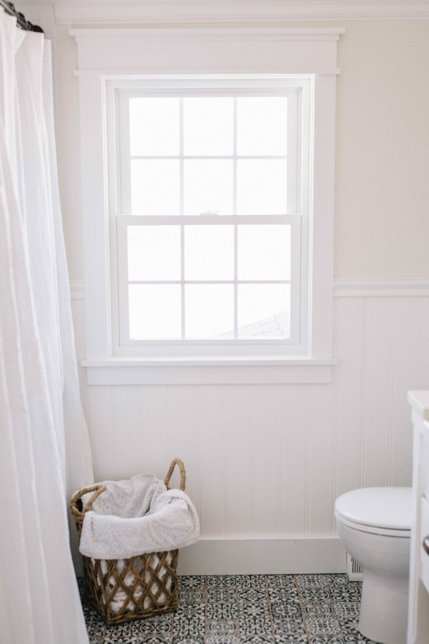 Farmhouse Bathroom Makeover // Bathroom Renovation Ideas with sliding barn door, medicine cabinets & black and white tile floors